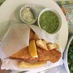 Fish and chips with mushy peas, tartar sauce, and a green salad