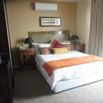 Room with queen bed.  There's a stocked fridge, coffee/tea maker, safe, ample bedside lighting.