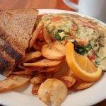 Omelete de rúcula, com queijo e tomate. Acompanha batatas e pão. Experimente, é delicioso.