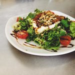 Caramelized pear and goats cheese salad topped with walnuts and herbs