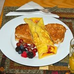 Breakfast of your choice - ham/bacon omelet served with whole grain organic toast and fresh frui