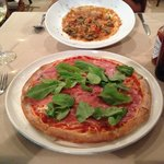 black gnocchi with crab sauce and a pizza with prosciutto and arugula