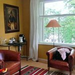 Room 1 lounge area with coffee machine and Herengracht outside the window