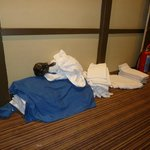 Full bag of garbage on top of clean sheets and towels dropped in the corridor