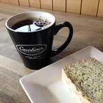 A cup of coffee with our house made lemon poppyseed bread