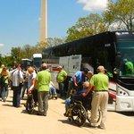 WW II Veterans getting off 3 busses to visit their memorial