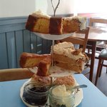 Cake stands with scones and four cakes: lemon, apple, carrot and almond, and walnut and coffee