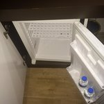 Mini fridge stocked with complimentary water daily