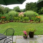 A lovely flower garden patio with tables and chairs