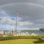 Early morning with USS Arizona Memorial in far distance, under rainbow & right of flagpole.
