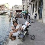 Tourists dangling their feet in the canal whilst baby sleeps