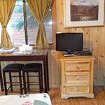 sitting on bed, looking toward small TV, table and stools Cozy Cabin #9