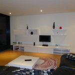 imagens da sala onde está uma pequena e única TV do ótimo apartamento