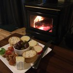 Complementary cheese and crackers platter next to the fireplace