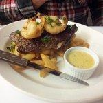 Porterhouse steak with battered prawns, steak chips and garlic sauce.