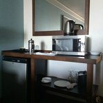 French press, fridge and microwave. Glasses and plates.