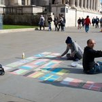 Chalk artists drawing out the world flags