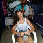 Sandra braiding our daughters hair at the shops on the beach