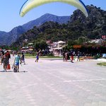 Paragliders landing in front of the restaurant area.