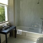 Look into the bathroom with bathtub and a shower extra