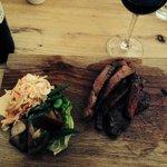 Rump steak with coleslaw and black tomato salad