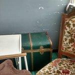 Balconcino con baule decrepito contenente coperte, sedia imbottita