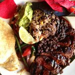 Hanger steak asada with fajita vegetables, pepian sauce, pico de gallo, guacamole, tortillas, an