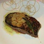 Rinds Entrecote mit einer Scheibe tranchiertem Knoblauchbund mit etwas Olivenöl und Fleischsaft
