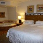 La grande chambre avec un lit king size et le jaccusi