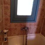 Room 4 clean bathroom, tiny bath and handheld shower and window facing corridor. Vague silhouett