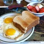 Breakfast of eggs , toast and fresh fruit.