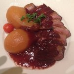Roast duck with raspberry sauce and pear.