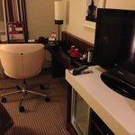 The flat screen TV and writing desk with chair.