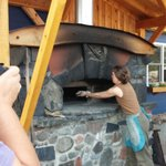 Tossing Carta di Musica cracker bread into the wood-fired oven