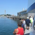 The P-town ferry docking at Fishernam's Pier with the Pilgrim's Monument in the background.
