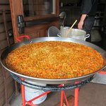Scrumptious Paella being cooked in a huge wok in the doorway