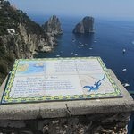 A sign explaining the Blue Lizard on Il Faraglioni which are in the background.