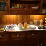Breakfast counter ready for the guests, including cold meats and cheeses, yoghurt, fresh fruit,