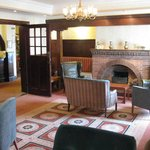 One of the lounges at the Cottage Hotel with the reception area beyond