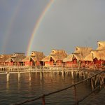 Water chalets under the evening rainbow