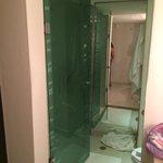 Looking into toilet/shower area- shower on left behind glass door.