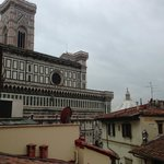 The view from my room's balcony (surrounded by apt. buildings and businesses, view of duomo)