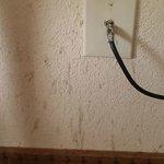 Drink splatter on wall by desk
