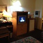 Dresser, CRT TV cabinet, micro, fridge, entrance to bathroom.