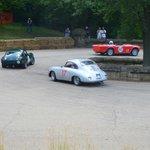 Triumph TR4, Triumph Spitfire, and Porsche at hairpin.