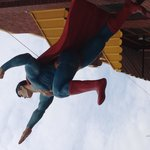 Superman takes flight from a nearby building
