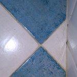podlaha v koupelně s cizími vlasy