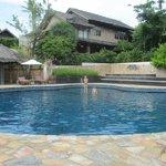 Warm en groot zwembad met ligbedden en parasols