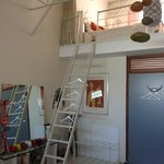 Interior of room showing ladder up to mezzanine