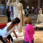 Tourguide Claire helping Charlotte better appreciate the masterpieces at the Louvre